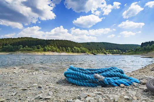 Blue rope on a pebble beach in the summer