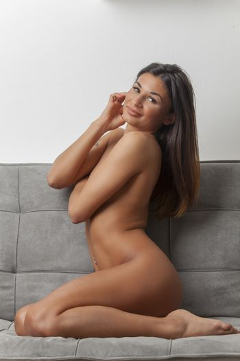 brunette woman kneeling on a couch
