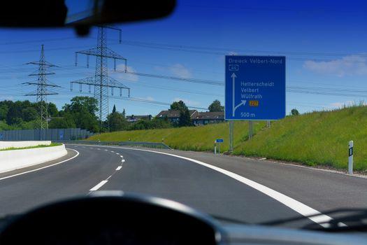 German motorway sign with inscription in German Driving direction to the cities - Velbert, Heiligenhaus, Wuelfrath and Hetterscheidt