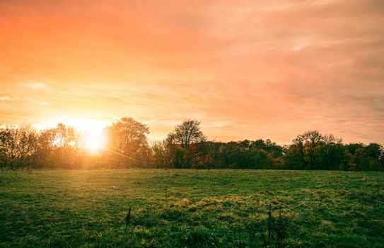 Rural landscape with a beautiful countryside sunset in red and orange colors with a green field in the front