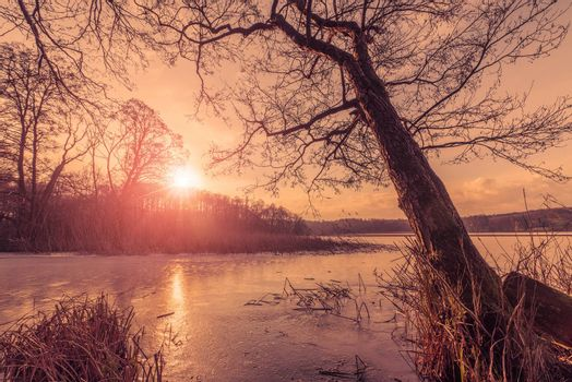 Sunset over a frozen lake in the winter with reflections of the sun on the cold ice