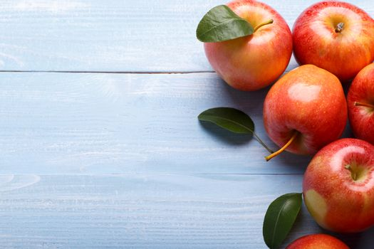 Autumn red apples on blue wooden table