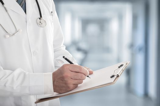Male doctor writing a note