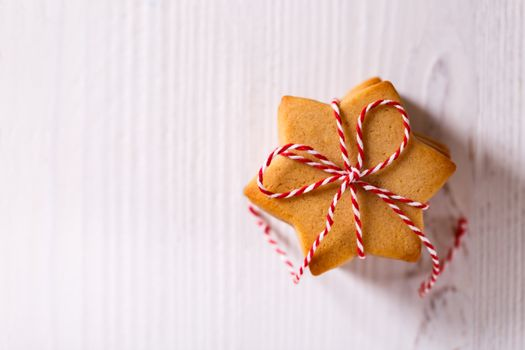 A stack of Christmas gingerbread shortbread cookies on white wooden table copy space flat lay