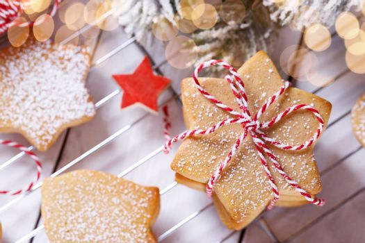 A stack of Christmas gingerbread shortbread cookies on white wooden table
