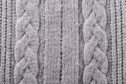 Background texture grey knitted plaid from woolen yarn, cozy winter autumn handmade sweater