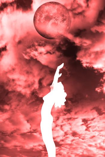 attractive silhouetted nude woman holding her hands up to the sky giving gratitude to the blood red moon in a yoga pose with a cloudy background