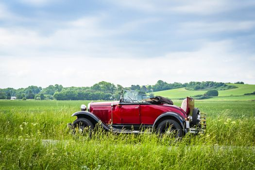 Red veteran car on a countryside road
