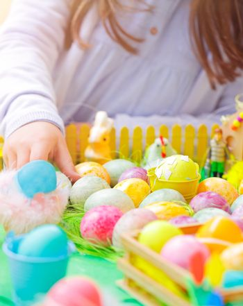 Closeup photo of a little girl's hand painting many colorful eggs, traditional Easter symbol, the winner of the eggs hunt, happy religious holiday