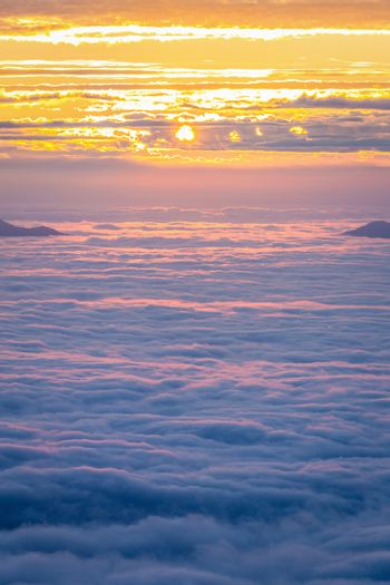 Aerial view of cloudy winter sky, fog and cloud cover mountain peak at sunrise of Phu Chi Fah, Chaingrai, Thailand.