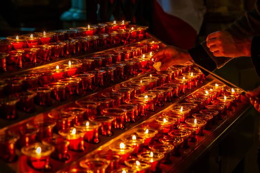 Red beewax candles in small glass cup on shelf in dark room are lighting up by worshiping prayers.