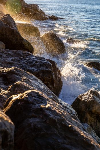 Moving wave and water of mediterranean sea touching rock beach making some  splashing water in the air at sunrise.