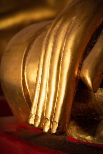 Vertical scene of close focus on fingers and hand of golden Buddha image as meditation posture represents highly concentration.