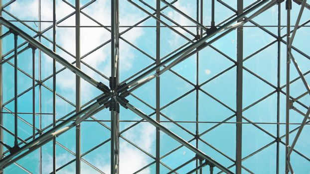 Structure of steel roof frame for building construction on sky background