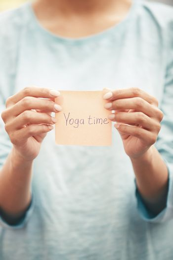 Woman holds adhesive note with Yoga time text