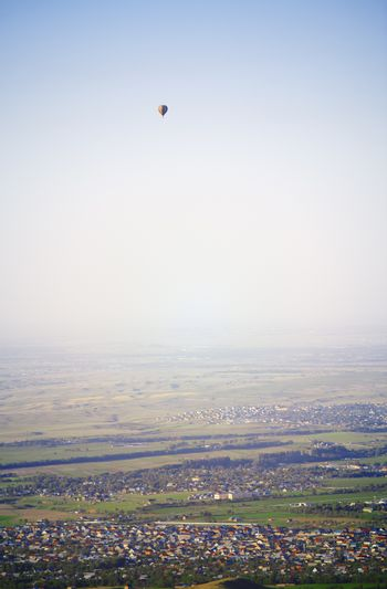 Hot air balloon above the green field and villages