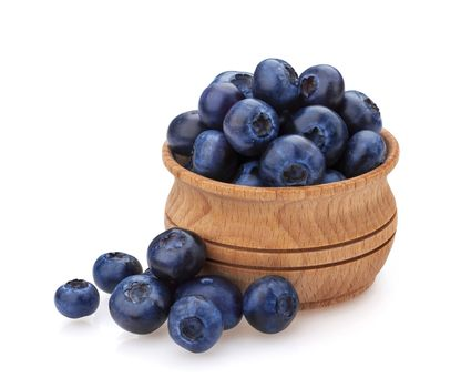 Blueberry isolated on white background. A pile of fresh blueberries in a wooden bowl