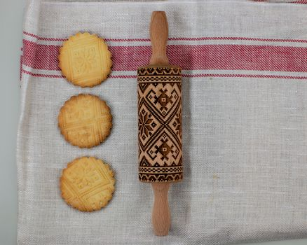 Cookies making concept, embossing roller, ready patterned shortbread, top view.