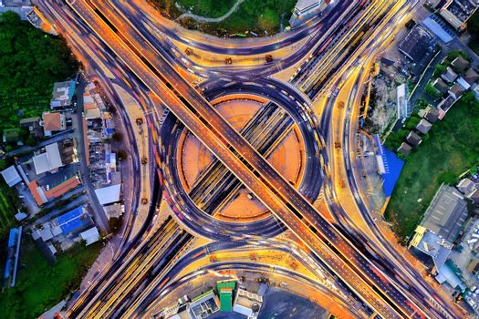 Aerial view of traffic in roundabout and highway at night.