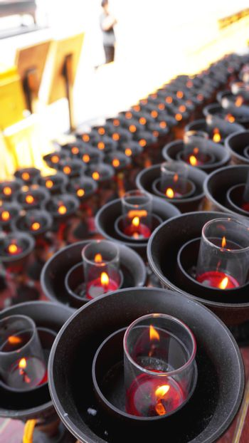 Burning big red candles in Buddhist temple