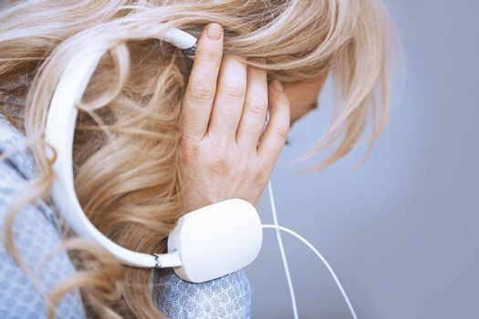 Blond woman listening music via headphones