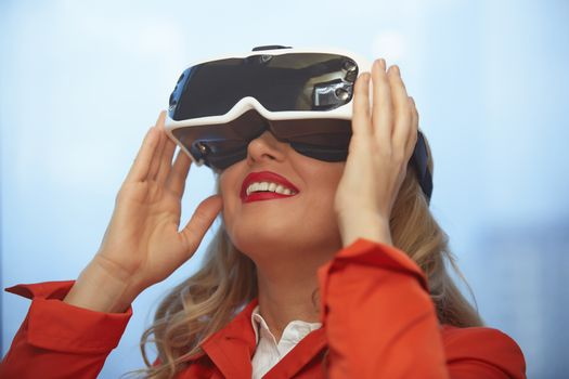 Woman in red coard using VR glasses headset