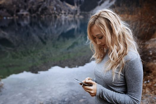 Woman using smartphone at the mountain lake