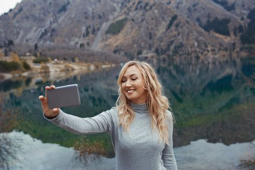 Smiling woman makes selfie at the mountain lake