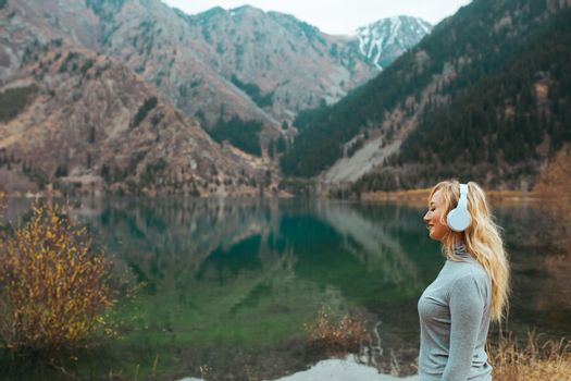 Woman wearing wireless headphones at the mountain lake