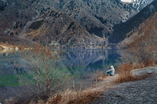 Woman listening music at the water's edge of mountain lake