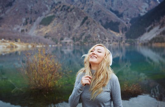 Woman wearing wireless headphones at the lake