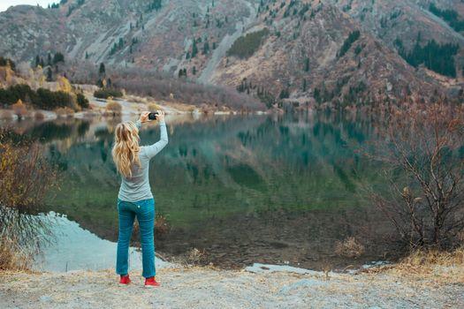Woman making mobile photo at the mountain lake