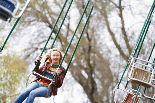 Blond woman riding on a chain swing