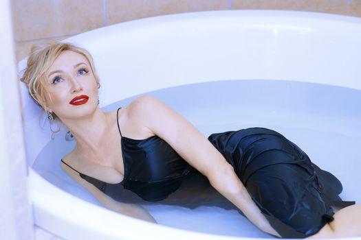 Woman wearing slip dress relaxing in the bath