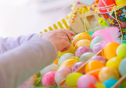 Closeup photo of a colorful painted eggs, child making handmade crafts for great religious holiday, happy Easter tradition