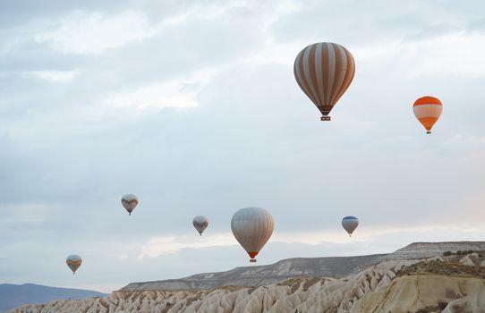 Hot air balloons flying over the rocks of Cappadocia, Turkey