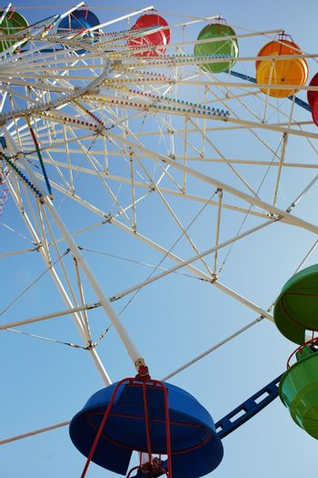 Ferris wheel in public amusement park. Low angle view