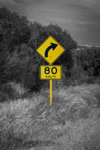 Street sign in Australia warning right curve ahead speed 80 in black and white with yellow accent color