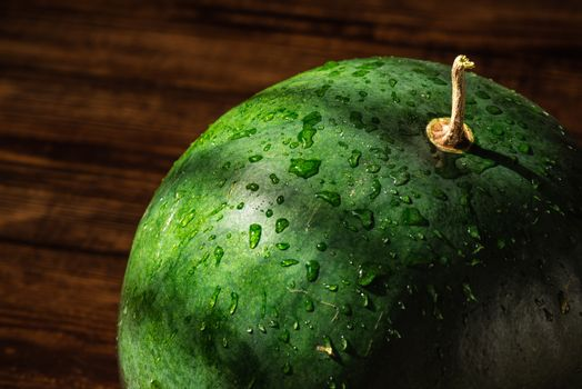 Green watermelon with sprays and shadows on peel