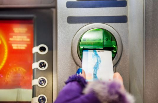 Hands of woman with gloves pulls in debit card