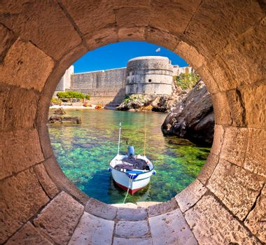 Dubrovnik small harbor under city walls view through stone carve