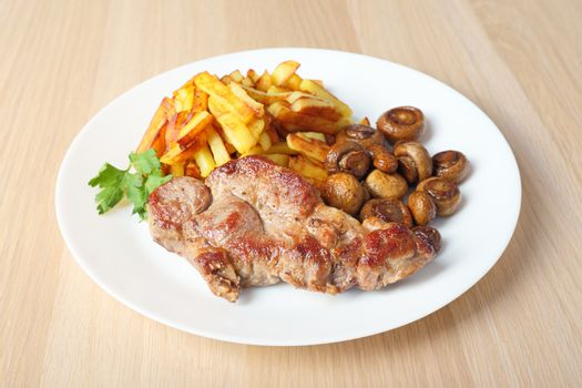 steak with fried potatoes and mushrooms side view