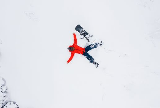 Aerial view of a man lying in the snow next to his snowboard