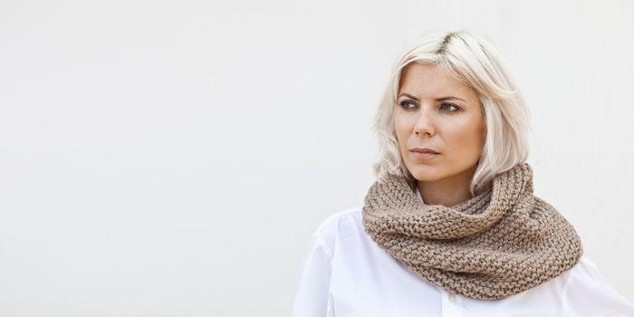 Woman in warm beige wool knitted snood