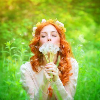 Beautiful female blowing on a dandelion flowers