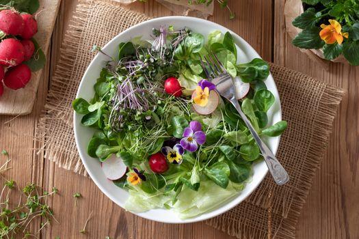 Salad with edible pansies and fresh broccoli and kale microgreen