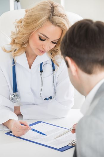 Doctor with patient reading a contract document in clinical office
