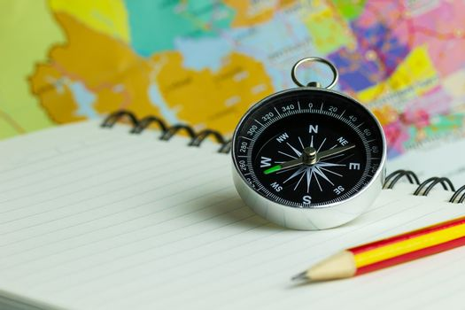 Compass notebook and pencil laid on a paper map. The concept rec