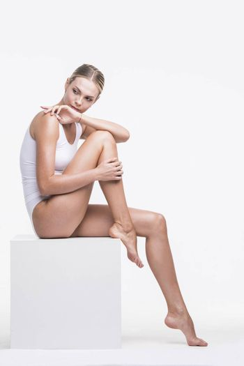 Young beautiful woman in cotton underwear sitting on white cube