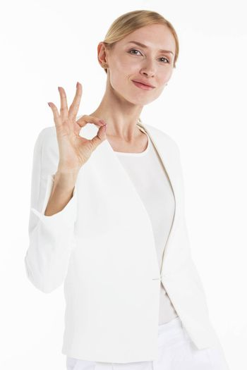 Beautiful mid adult businesswoman showing okay hand sign gesture isolated on white background